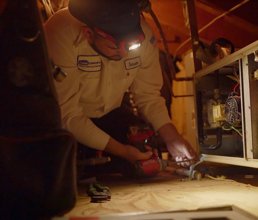 An employee repairing an AC unit in an attic