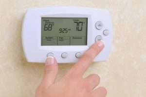 a hand touching a thermostat