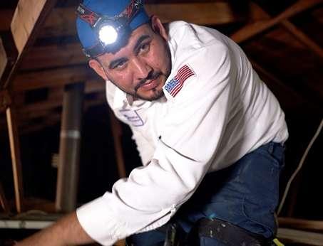 An AC technician working in an attic
