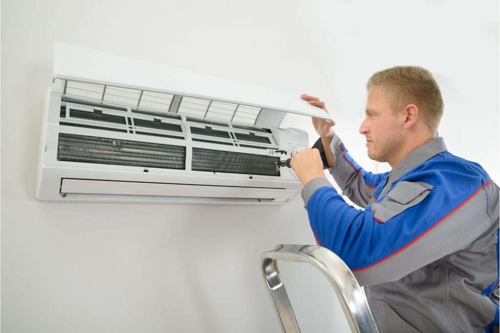 man fixing air conditioner mini split unit