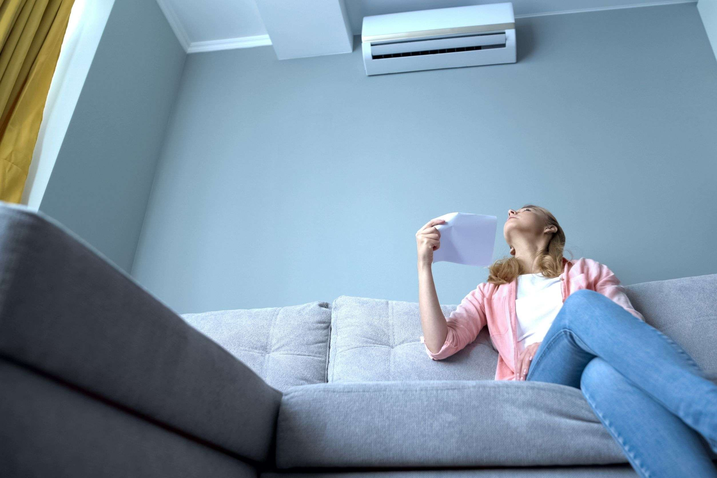 woman using paper to refresh herself because her AC is not cooling