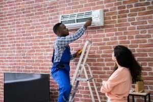 Tech doing an AC repair, homeowner waiting on tech to do AC repair