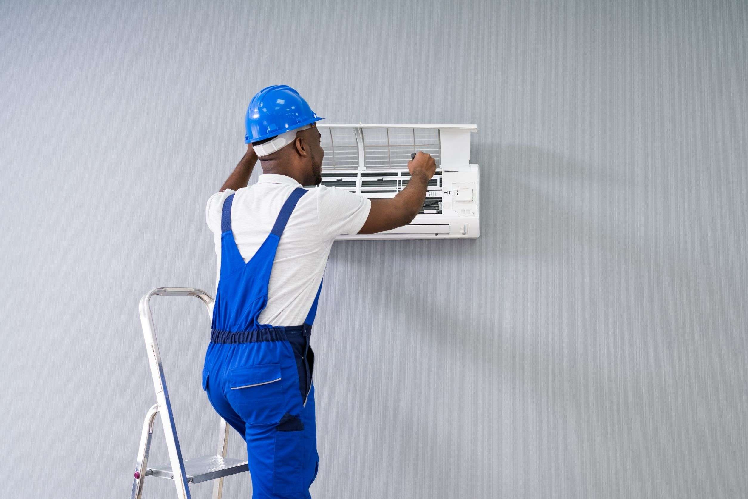 tech from HVAC company working on AC unit