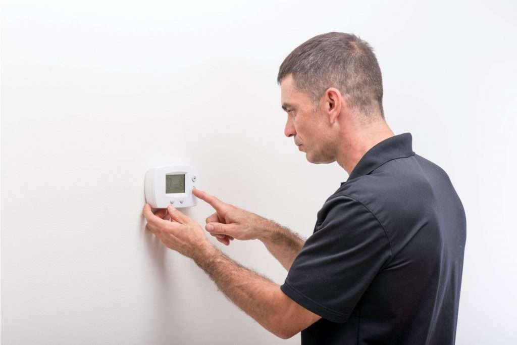 HVAC tech fixing thermostat malfunctions