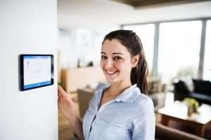 woman standing next to a smart thermostat