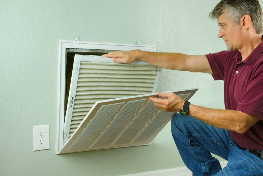 homeowner checking if it is time for HVAC maintenance